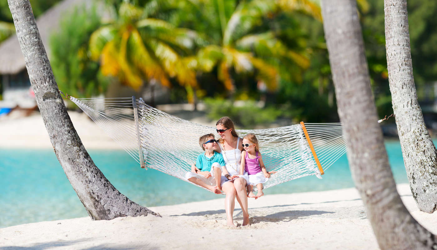 Mother and two kids relaxing on hammock at tropical beach